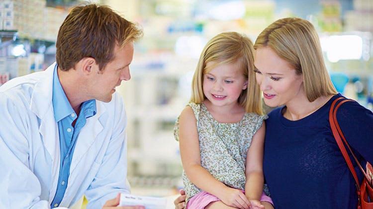 фармацевт, разговаривающий с мамой и ребенком