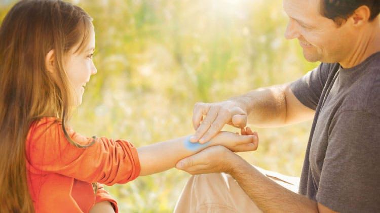 отец, мажущий ребенка солнцезащитным кремом