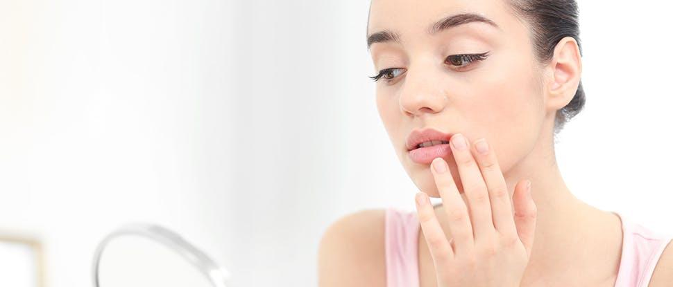 обеспокоенная женщина, трогающая губу