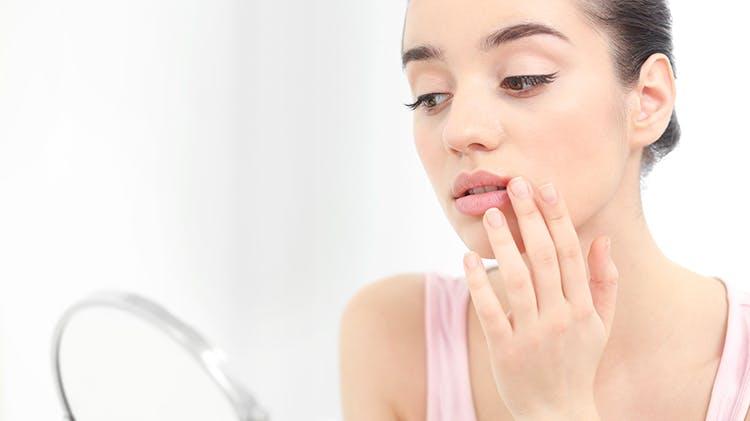 Изображение женщины, трогающей губу