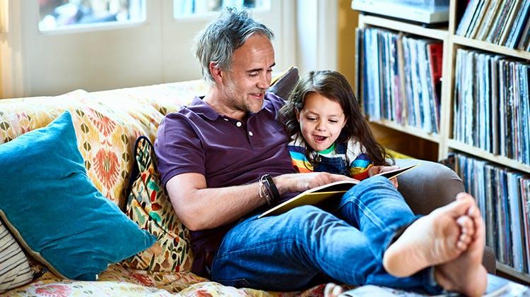 Çocuğuna kitap okuyan adam