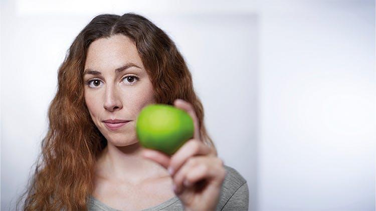 Elinde elma tutan bir kadın