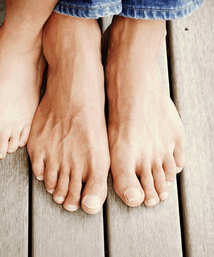 Две пары босых стоп на деревянном полу