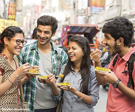 Young group of friends laughing and eating street food/chaat