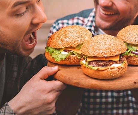 Três adultos posando para uma foto com dois mordendo hambúrgueres.