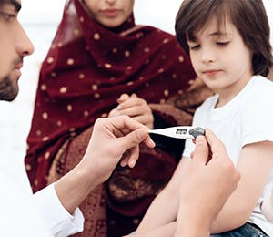 طبيب يأخذ حرارة طفل