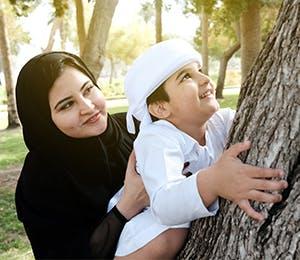 أم تمسك ابنها وهو يتسلّق شجرة
