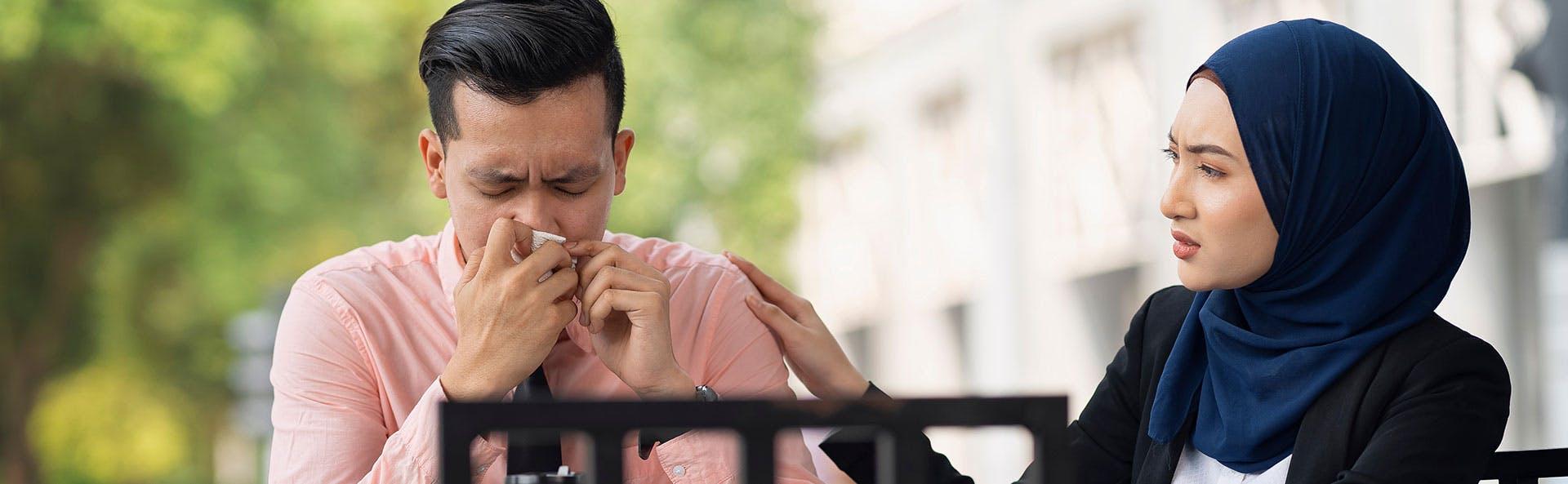 رجل يعاني من زكام وامرأة بقربه