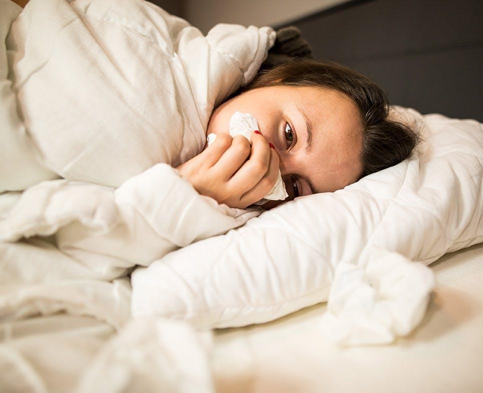 امرأة في السرير تشعر بالزكام