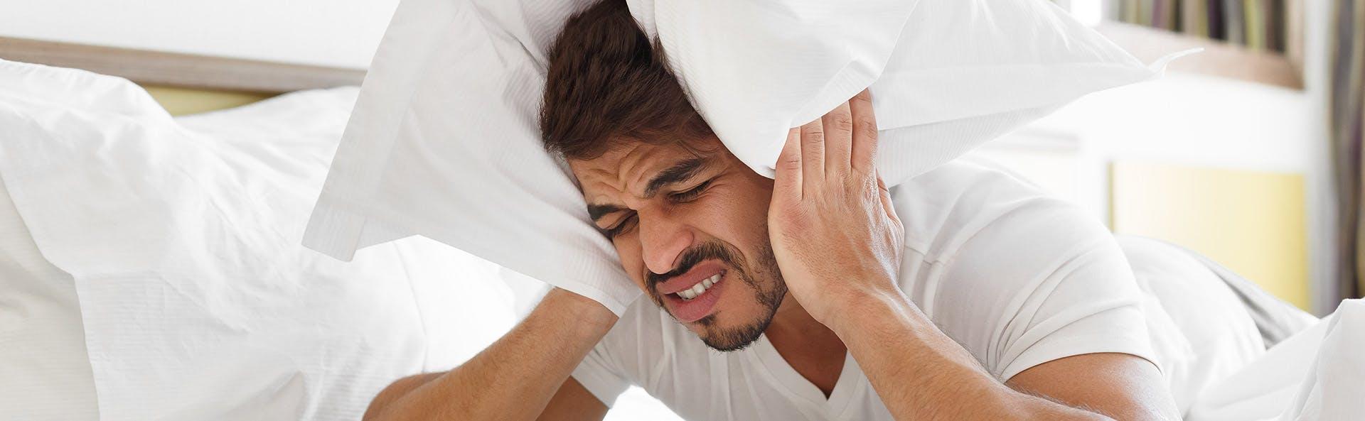 رجل في السرير يعاني من صداع نصفي شديد