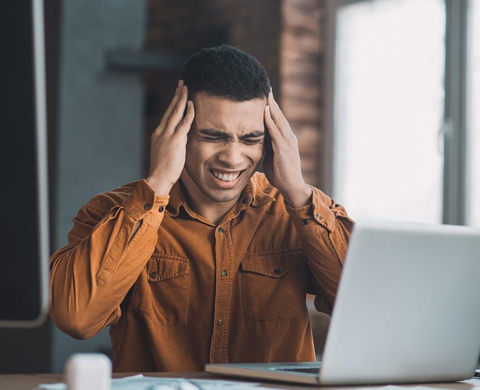 رجل يعاني من صداع شديد بعد جهد في العمل