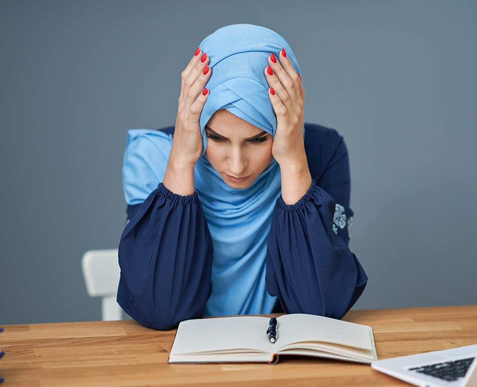 امرأة تقرأ لكنها تشعر بصداع