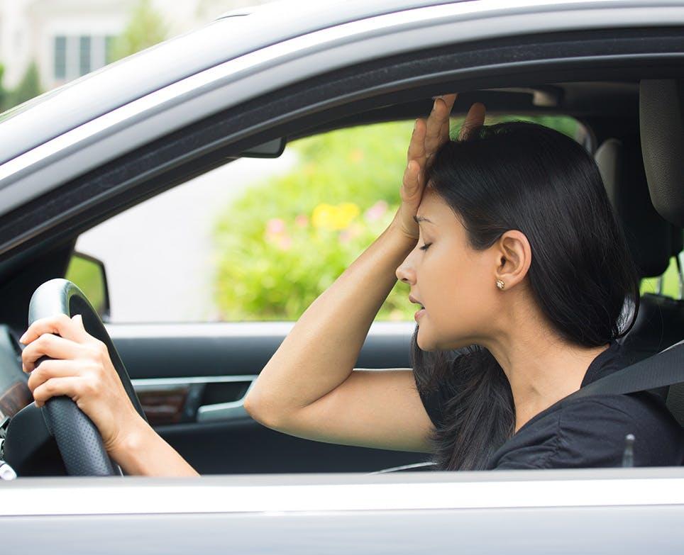 امرأة تقود سيارتها وهي تعاني من ألم الرأس