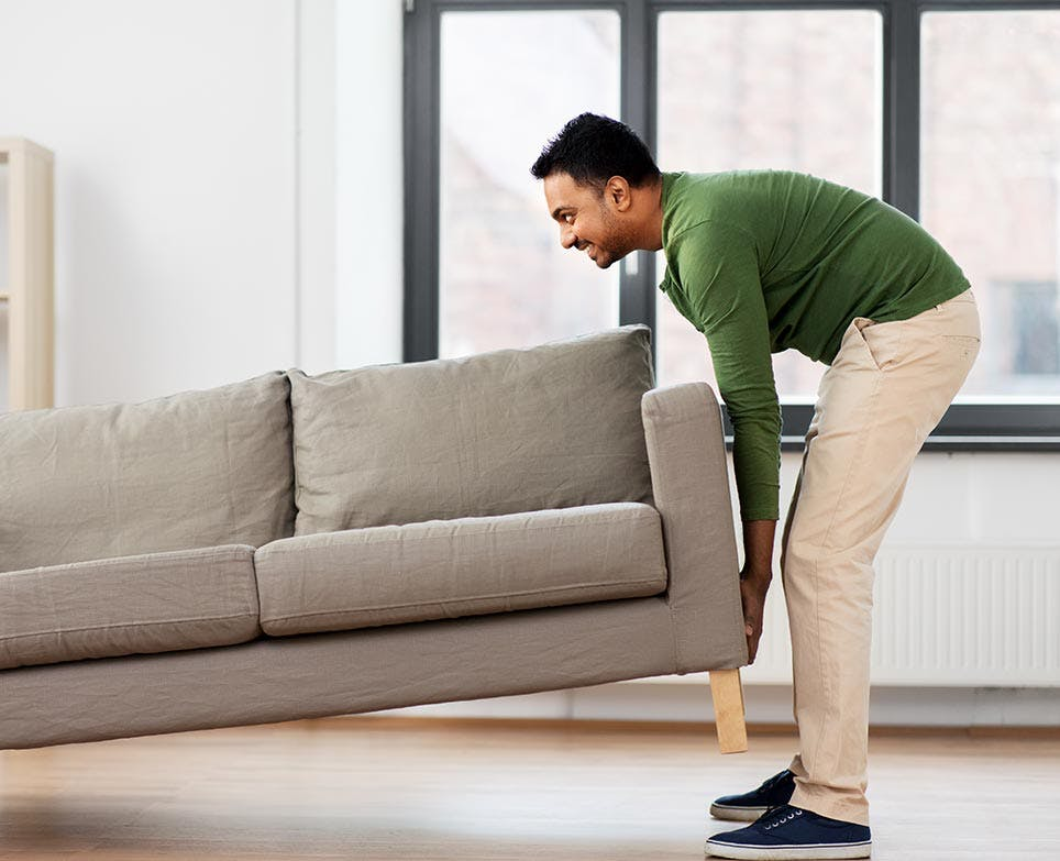 رجل يرفع الأريكة