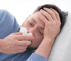 Man with flu symptoms blowing his nose.