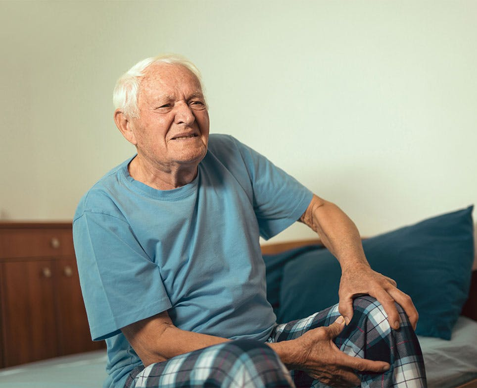 Older adult holding his sore knee.