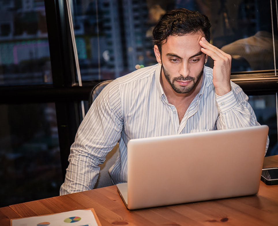 Man in front of a laptop with a headache.
