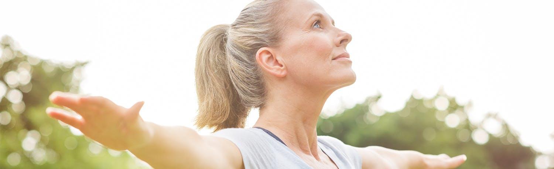 Older woman doing yoga outdoors