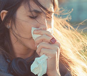 Mujer limpiando su nariz.