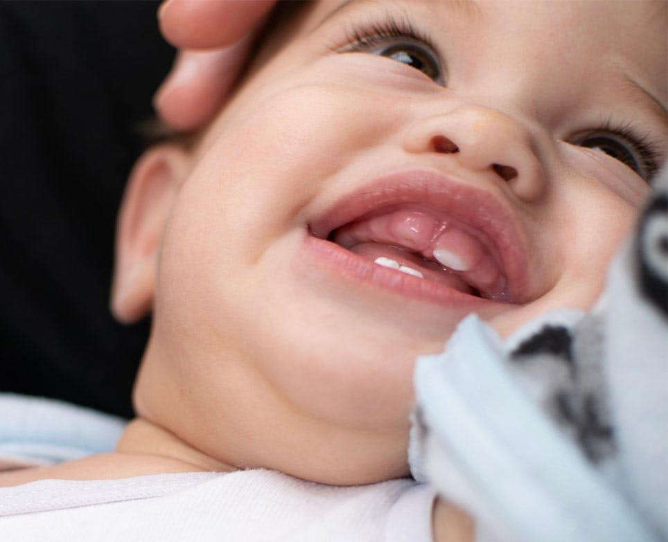 Bebé sonriendo, en proceso de dentición.
