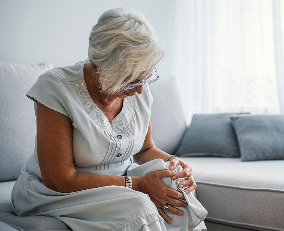 Mujer mayor sujetando su rodilla en señal de dolor.
