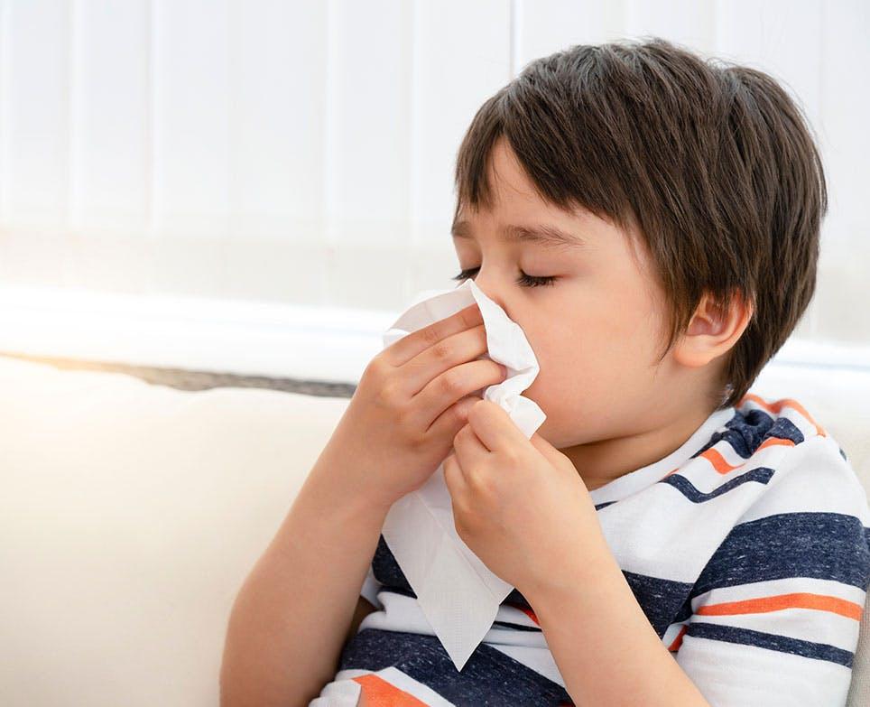 Niño limpiando su nariz con pañuelos desechables.