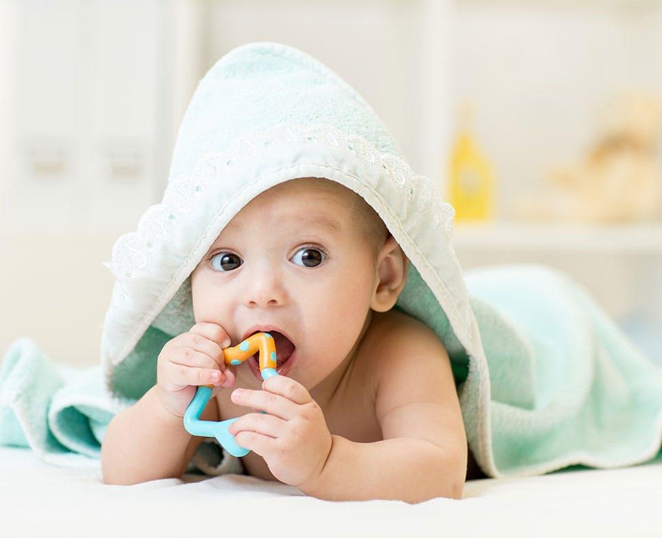Bebé mordiando un juguete para dentición después de un baño.