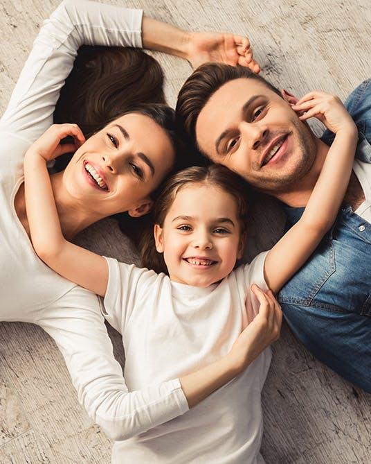 Padres sonriendo con su hija.