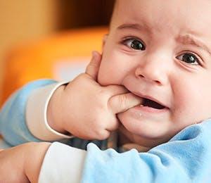 Bebé con sus dedos en la boca.