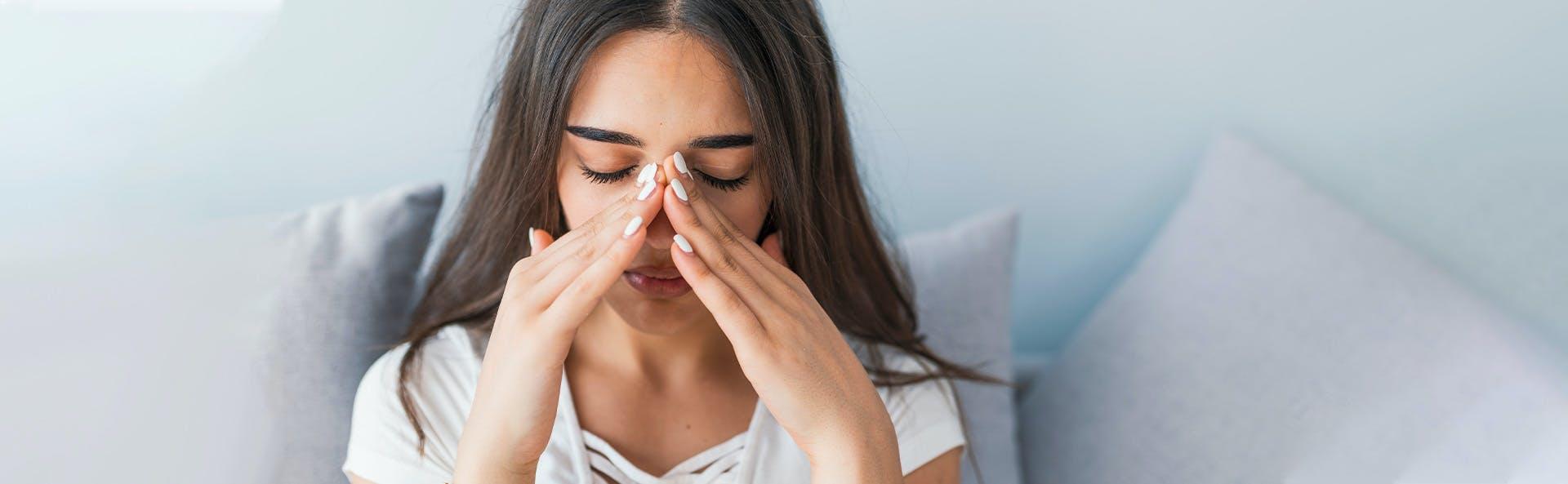 Mujer joven tocándose la nariz en señal de dolor.