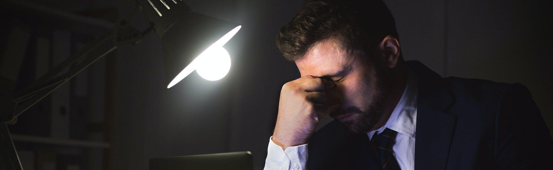 Hombre en la penumbra se toca la parte superior de la nariz en señal de dolor.