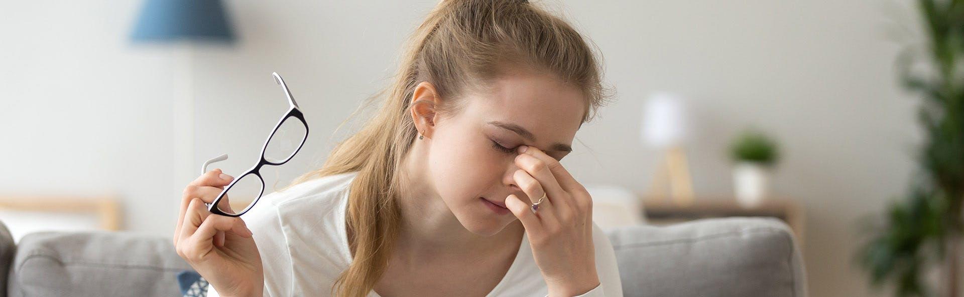 Mujer joven retirándose las gafas, se toca la nariz en señal de dolor.