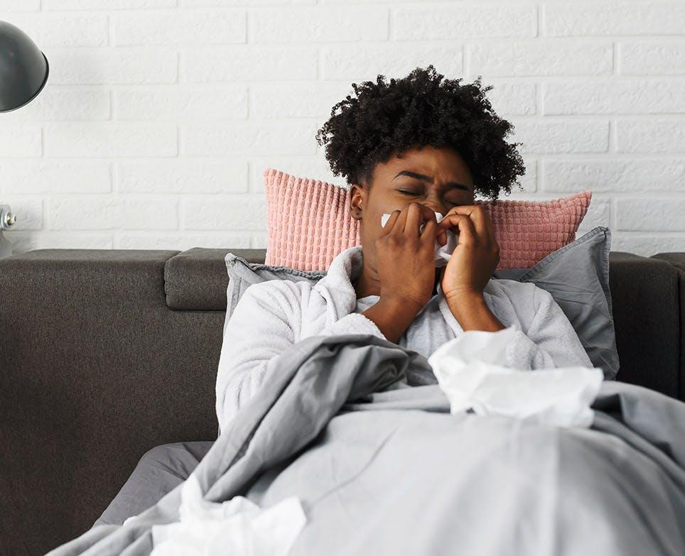 Mujer recostada en su cama con congestión nasal, limpiando su nariz.