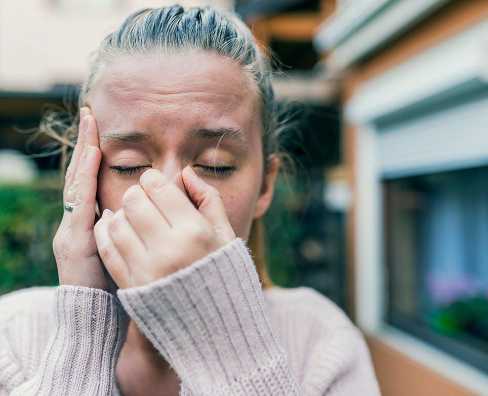 Mujer joven con dolor en la nariz y la cabeza.