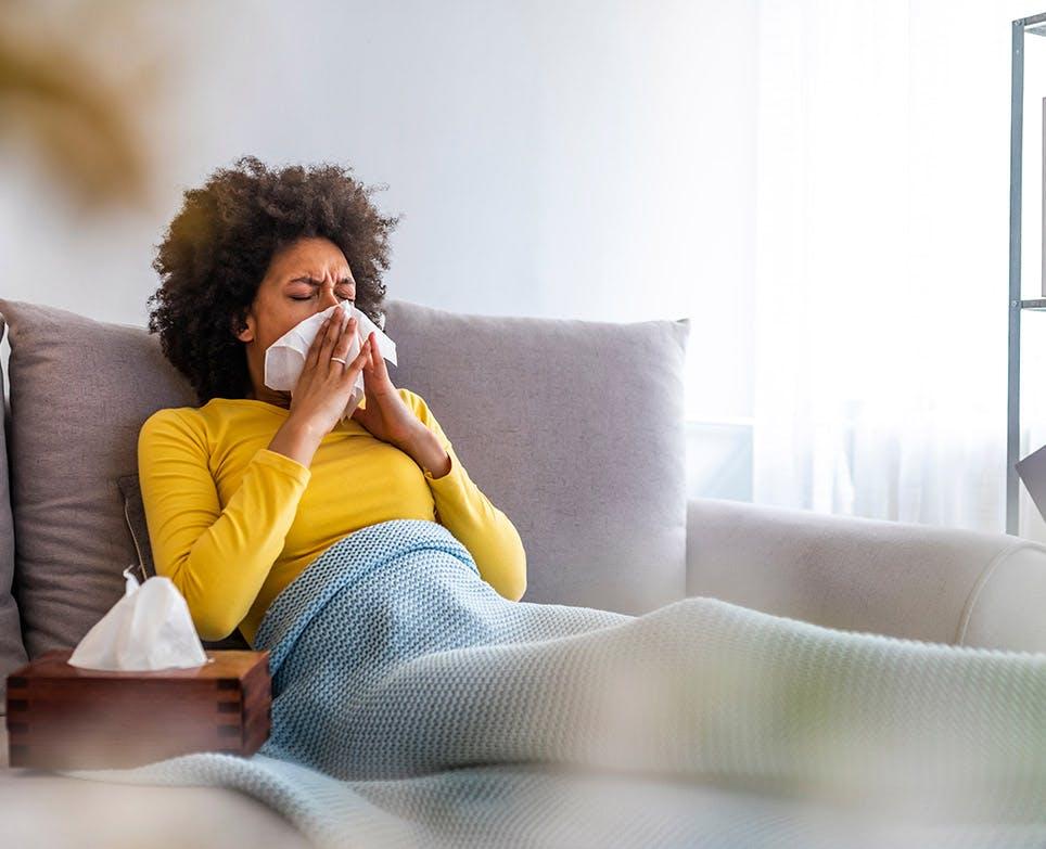 Mujer con congestión nasal, sentada en un sofá, limpiando su nariz.