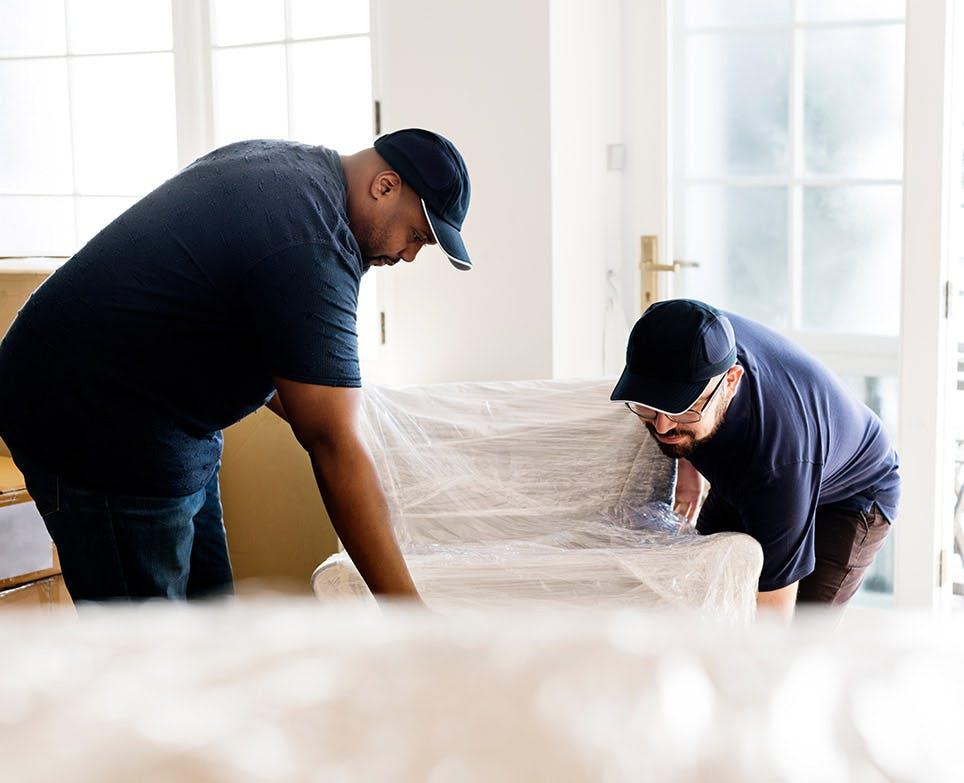 Dos hombres levantando un mueble.