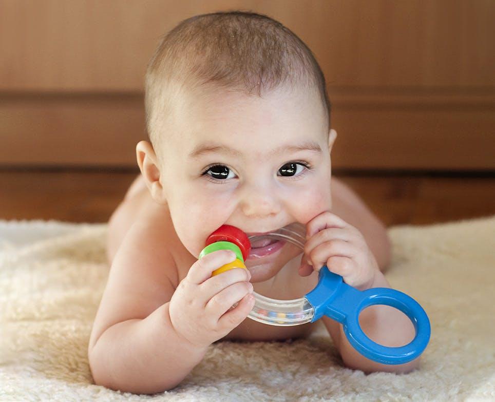 Bebé mordiando un juguete para dentición.