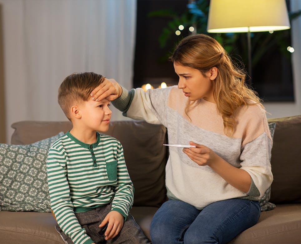 Madre leyendo la temperatura de su hijo.