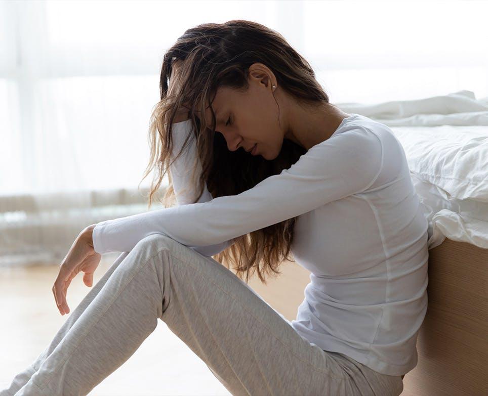 Mujer sentada en el suelo, se toca su cabeza en señal de dolor.