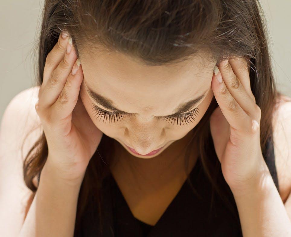 Mujer se toca los costados de su cabeza en señal de dolor.