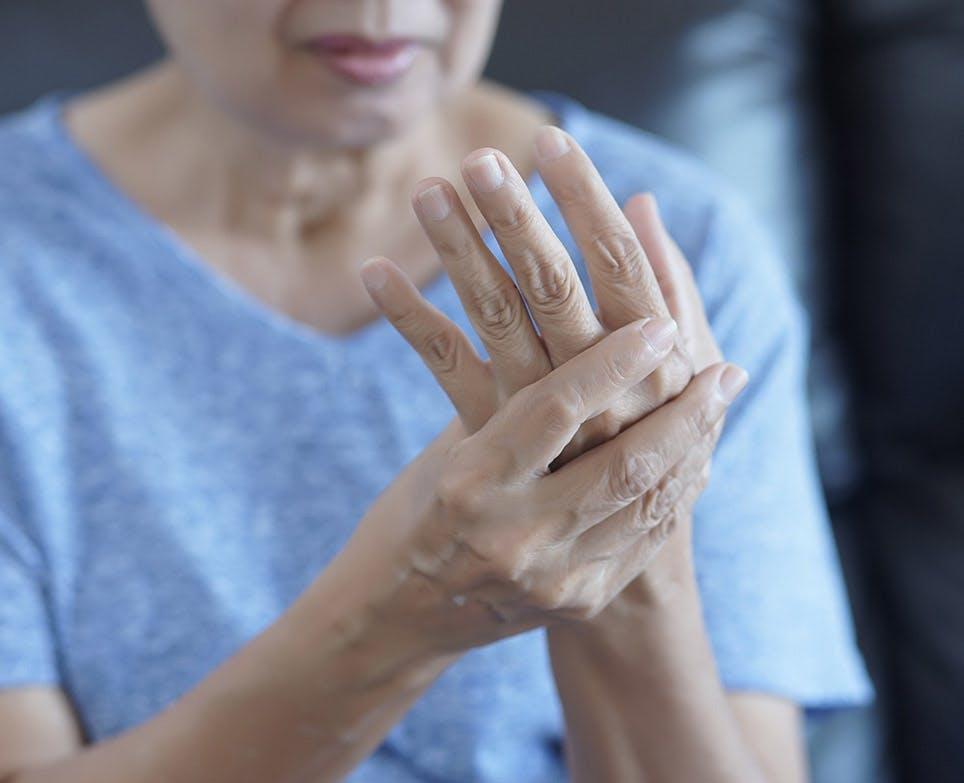 Mujer mayor sujetando su mano en señal de dolor.