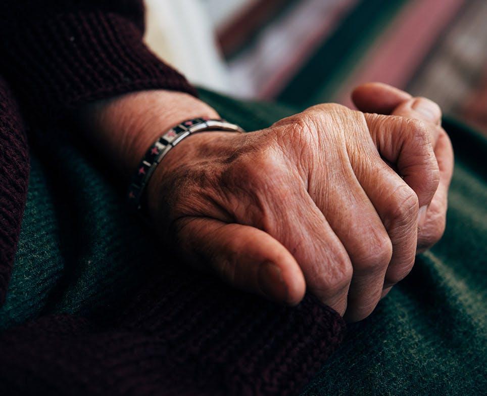 Representación de dolor en las manos en un adulto mayor.