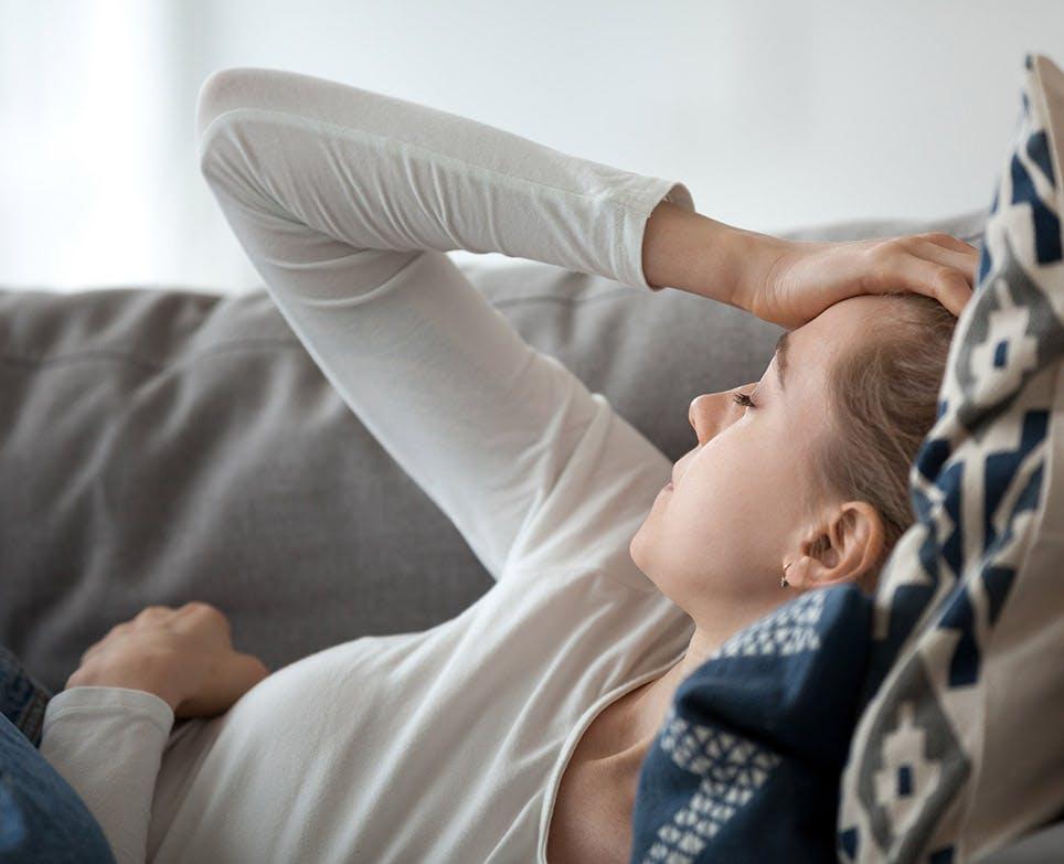 Mujer recostada se toca la cabeza en señal de dolor.