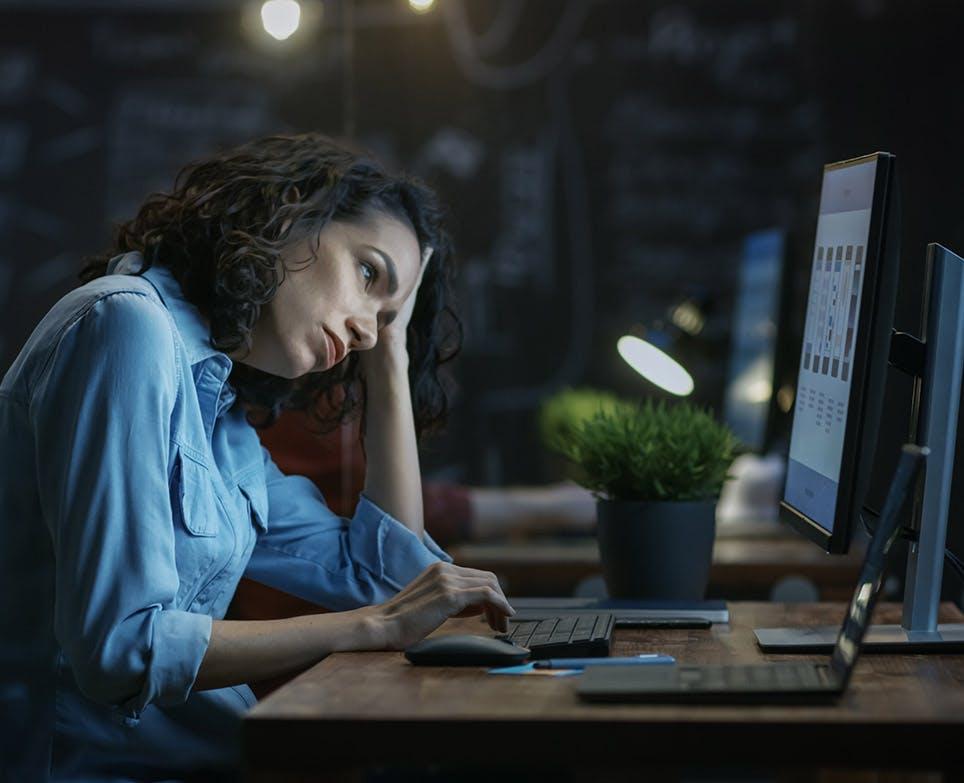Mujer frente al computador se toca la cabeza en señal de dolor.