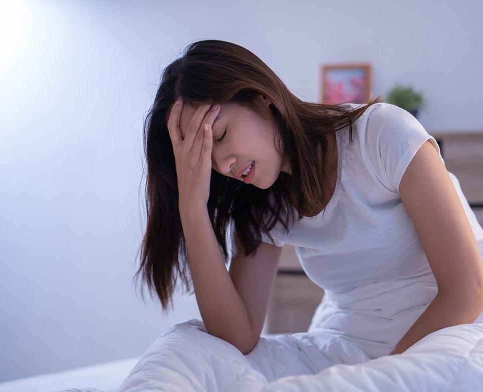 Mujer joven se toca la cabeza en señal de dolor.
