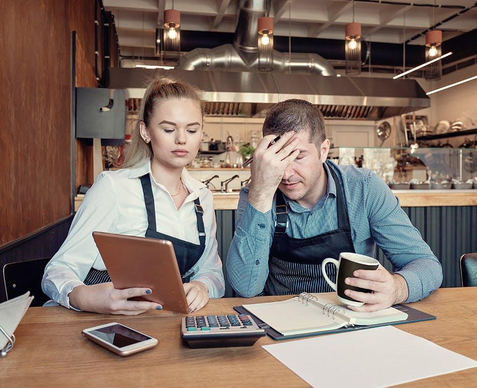 Pareja trabajando. El hombre se agarra la cabeza en señal de dolor.