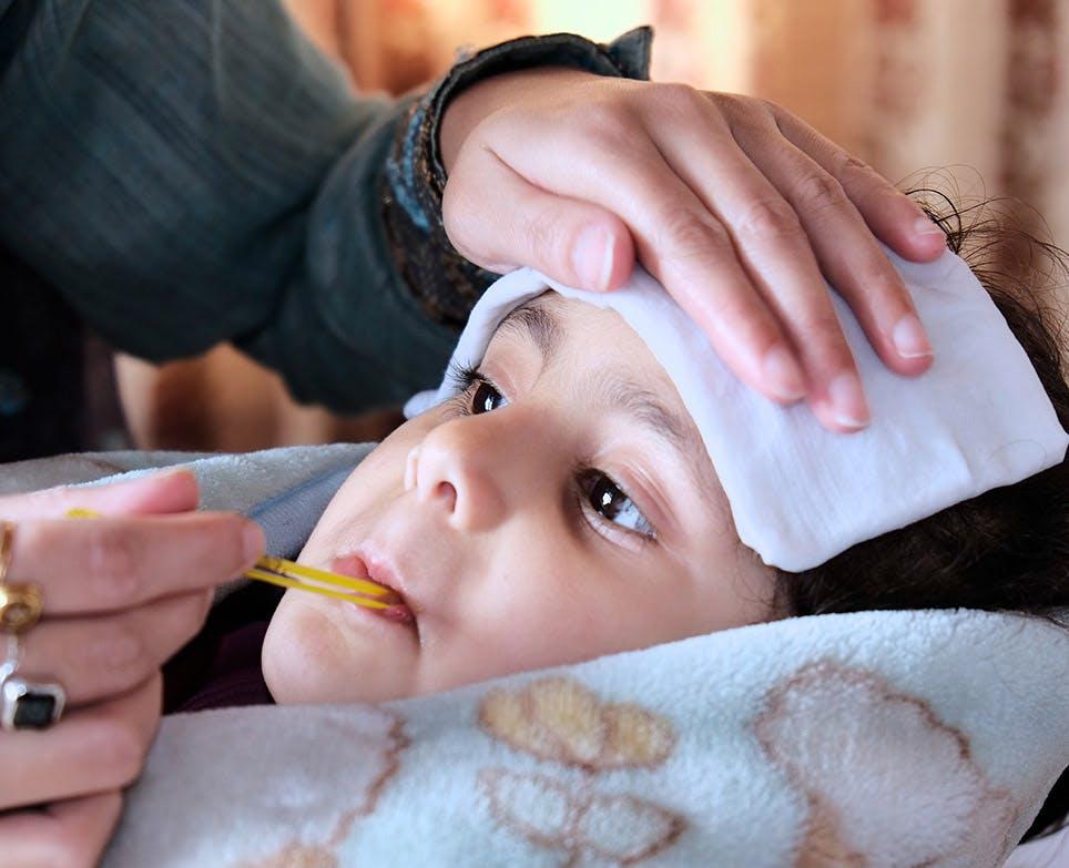 Toma de temperatura de un niño con termómetro de vidrio.