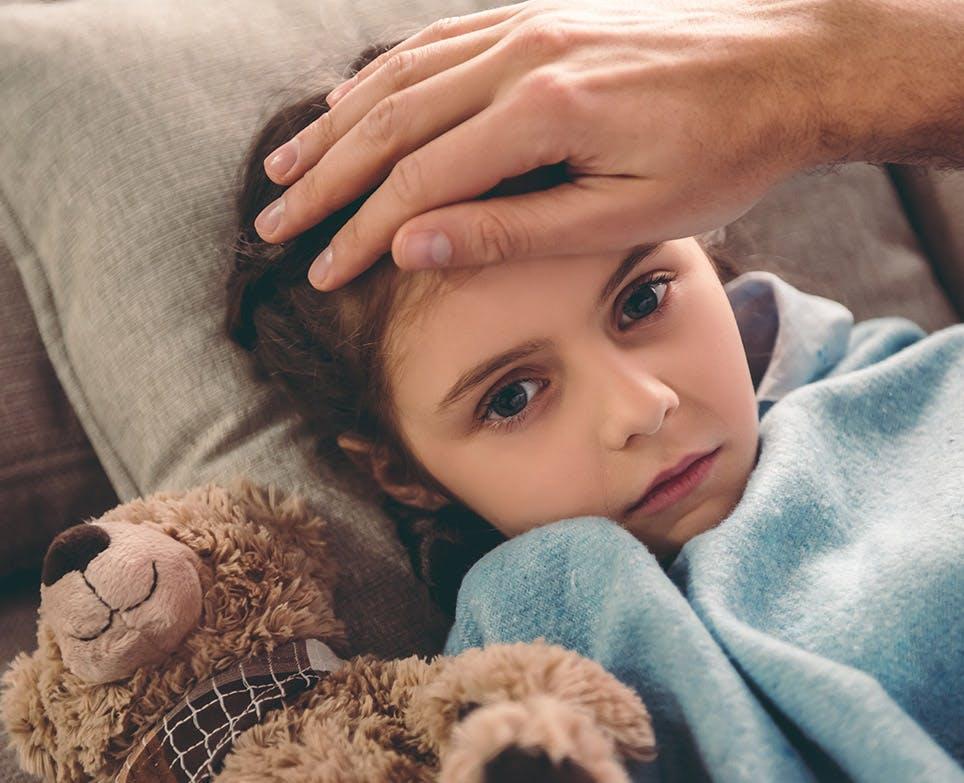 Mano de un hombre en la frente de una niña.