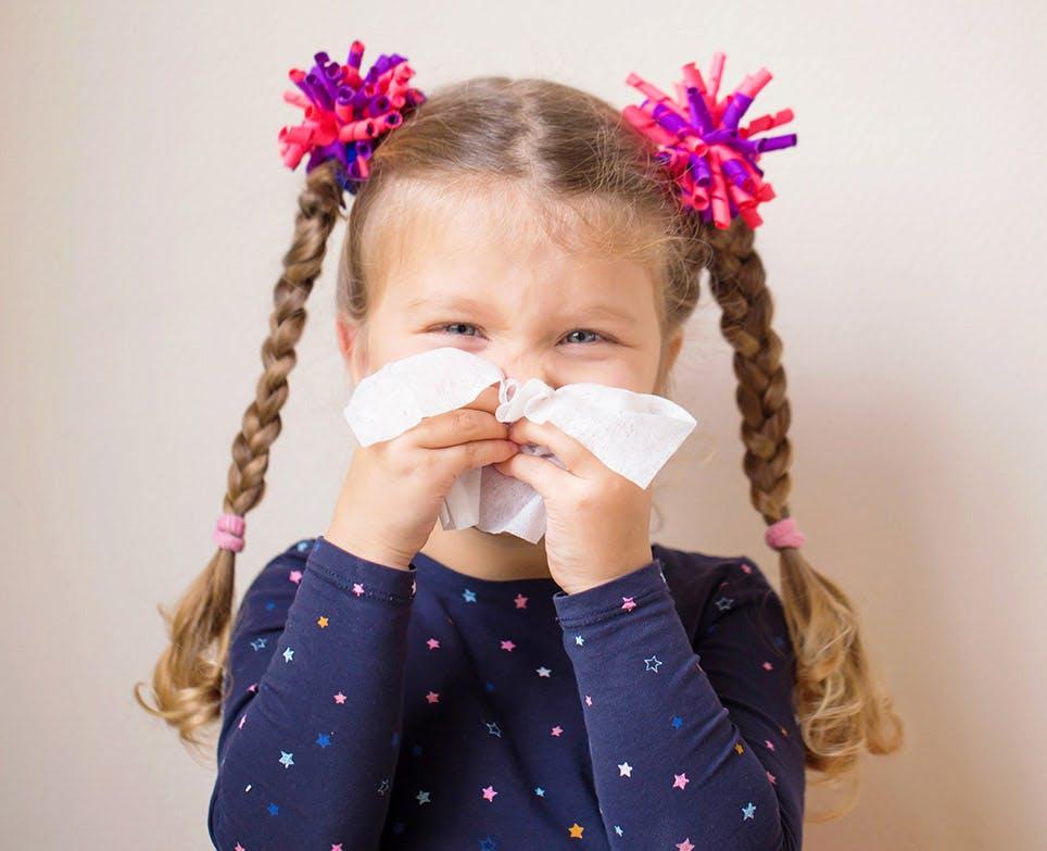 Niña limpiando su nariz con pañuelos desechables.