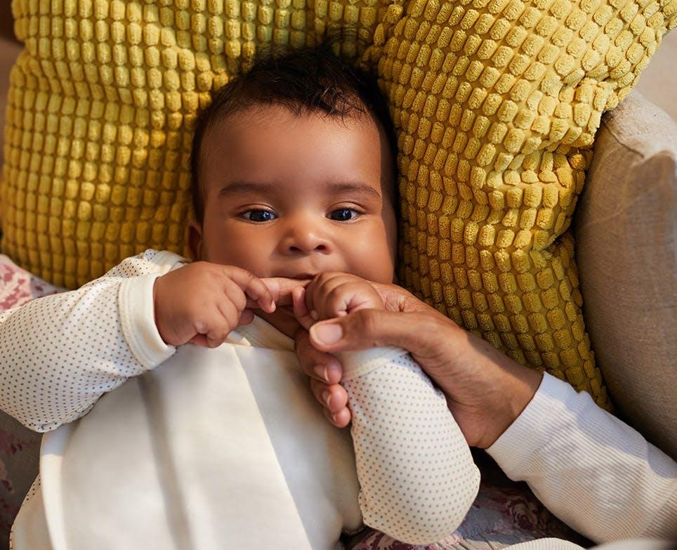Bebé mordiendo el dedo de una persona.